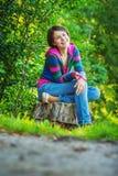 La ragazza si siede sul troncone Immagine Stock Libera da Diritti