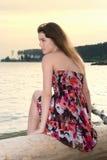 La ragazza si siede sull'albero sul litorale di mare Immagini Stock Libere da Diritti