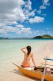 La ragazza si siede sulla barca sulla spiaggia bianca fotografie stock libere da diritti