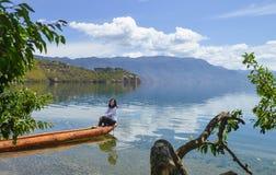 La ragazza si siede sulla canoa, sorridente immagine stock libera da diritti