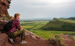 La ragazza si siede sulla montagna e esamina la distanza fotografie stock