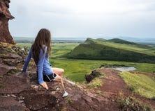 La ragazza si siede sulla montagna e esamina il lago fotografia stock