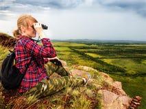 La ragazza si siede sulla montagna e esamina la distanza con il binocolo immagine stock libera da diritti