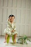 La ragazza si siede sulla presidenza Fotografia Stock