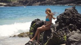 La ragazza si siede sulla roccia ed esamina il mare Bali, Indonesia fotografie stock libere da diritti