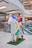 La ragazza si siede sulla scultura del cavallo al centro commerciale di Livat, Pechino, Cina Fotografia Stock Libera da Diritti