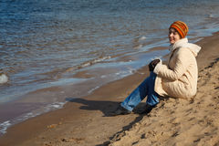 La ragazza si siede sulla spiaggia, un giorno pieno di sole di autunno Fotografie Stock Libere da Diritti