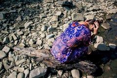 La ragazza si siede sulle rocce che girano intorno con lei di nuovo al fotografo Fotografia Stock