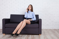 La ragazza si siede sullo strato e sul telefono di conversazione Fotografia Stock Libera da Diritti