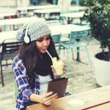 La ragazza si siede in un caffè che ascolta la musica che beve un cocktail tropicale e che per mezzo della compressa digitale Fotografia Stock