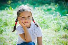 La ragazza si siede in un parco Immagini Stock Libere da Diritti