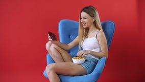La ragazza si siede in una sedia, guardante un film sul telefono e mangiante il popcorn archivi video