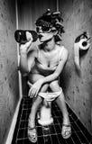 La ragazza si siede in una toletta Fotografia Stock