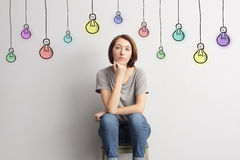 La ragazza si siede vicino alla parete su fondo delle lampadine disegnate colorate Immagini Stock Libere da Diritti