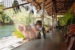 La ragazza si trova in hammock Fotografia Stock
