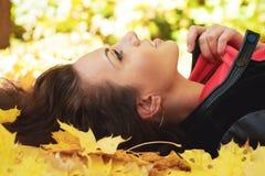 La ragazza si trova nelle foglie gialle Fotografia Stock Libera da Diritti