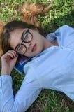 La ragazza si trova sull'erba Immagini Stock Libere da Diritti