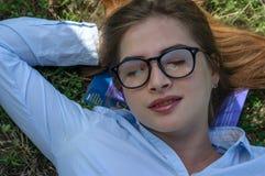 La ragazza si trova sull'erba Fotografie Stock Libere da Diritti