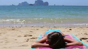 la ragazza si trova sulla spiaggia in mare contro le isole stock footage