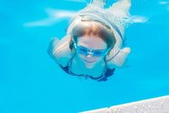 La ragazza si tuffa e nuota sotto l'acqua nello stagno con i vetri FO Fotografia Stock