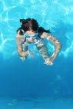 La ragazza si tuffa l'acqua blu dello stagno Immagine Stock Libera da Diritti