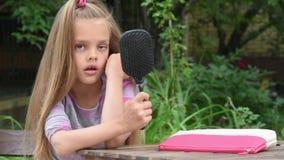 La ragazza si vede in uno specchio costruito nel pettine ed in hamming stock footage