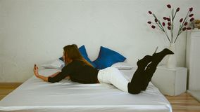 La ragazza snella si trova in stivali sul letto e fa una foto stock footage