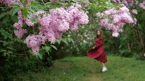 La ragazza snella in un vestito sciolto cammina allegro attraverso il giardino stock footage