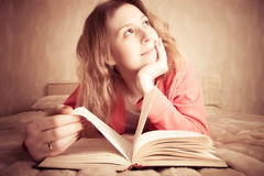 La ragazza sogna leggendo il libro Immagine Stock