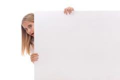 La ragazza sorpresa sta schioccando fuori dal lato dell'insegna in bianco bianca, isolato fotografie stock libere da diritti