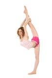 La ragazza sorridente in abiti sportivi fa l'esercitazione relativa alla ginnastica Fotografia Stock Libera da Diritti