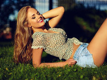 La ragazza sorridente alla moda in panno casuale luminoso in jeans mette all'aperto Immagine Stock