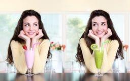 La ragazza sorridente in caffè beve la fragola ed il kiwi del frappé immagine stock
