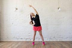 La ragazza sorridente che fa gli esercizi manda in aria l'interno Immagini Stock Libere da Diritti
