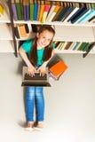 La ragazza sorridente che si siede sul pavimento con il computer portatile cerca Immagini Stock Libere da Diritti