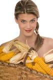 La ragazza sorridente che tiene un cestino ha riempito di cereale Fotografia Stock