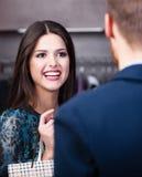 La ragazza sorridente comunica con assistente di negozio Fotografia Stock