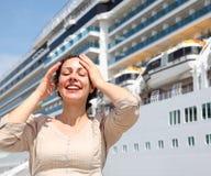 La ragazza sorridente con gli occhi chiusi si leva in piedi vicino alla nave fotografia stock libera da diritti