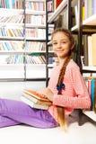 La ragazza sorridente con i libri si siede sul pavimento in biblioteca Fotografie Stock