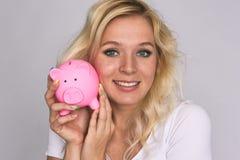 La ragazza sorridente con le lentiggini tiene un porcellino salvadanaio Fotografia Stock