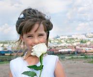 La ragazza sorridente con un bianco è aumentato Fotografia Stock Libera da Diritti