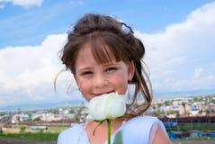 La ragazza sorridente con un bianco è aumentato Fotografie Stock