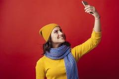 La ragazza sorridente con un telefono fa il selfie fotografia stock