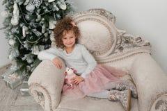 La ragazza sorridente del bambino con le pecore gioca al Natale Immagini Stock
