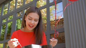 La ragazza sorridente del cliente sbircia il sacco di carta con i nuovi acquisti dal deposito di modo durante la vendita a venerd video d archivio