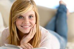 La ragazza sorridente dello studente ha letto il sofà di menzogne del libro Fotografia Stock