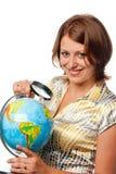 La ragazza sorridente esamina il globo Fotografia Stock