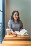 La ragazza sorridente gode del suo giorno con il libro ed il caffè Fotografia Stock