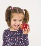 La ragazza sorridente graziosa insegna alla frutta della mela fotografia stock libera da diritti