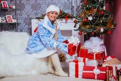 La ragazza sorridente mette i presente sotto l'albero di Natale immagini stock